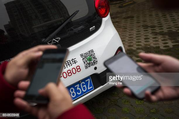 People use their iPhone to scan the QR code on the car on March 182017 in Wuhan Hubei province China The mostly electric share cars are ready for...