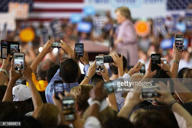 People use their mobile devices to record Democratic presidential candidate Hillary Clinton as she speaks during a campaign rally at the Sunrise...