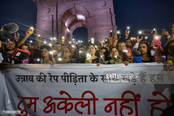 People use their mobile phones as torches while gathered for a silent protest in solidarity with the Unnao rape case victim, at India Gate on July...
