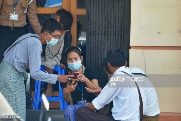 People use their mobile phones to check the connection and Facebook outside an internet shop in Naypyidaw on March 16 as Myanmar authorities ordered...