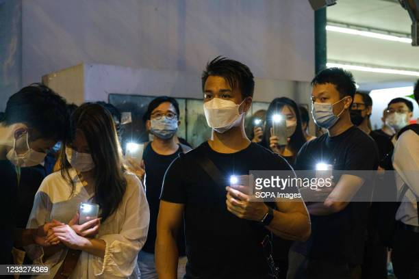 People use their mobile phones to shine light outside Victoria Park. Police has banned Hong Kongs annual Tiananmen vigil this year citing COVID-19...