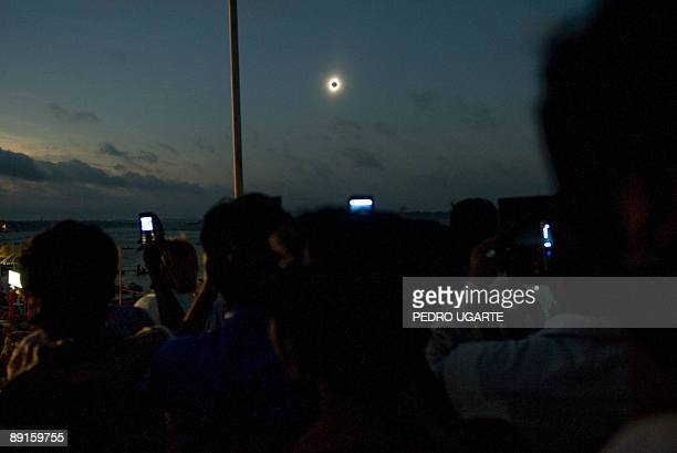 People use their mobile phones to take photos as they join thousands of people along the Ganges river to watch a solar eclipse in the Indian city of...