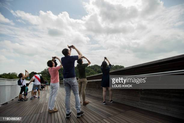 People use their mobile phones to watch as the moon moves in front of the sun in a rare ring of fire solar eclipse in Singapore on December 26 2019