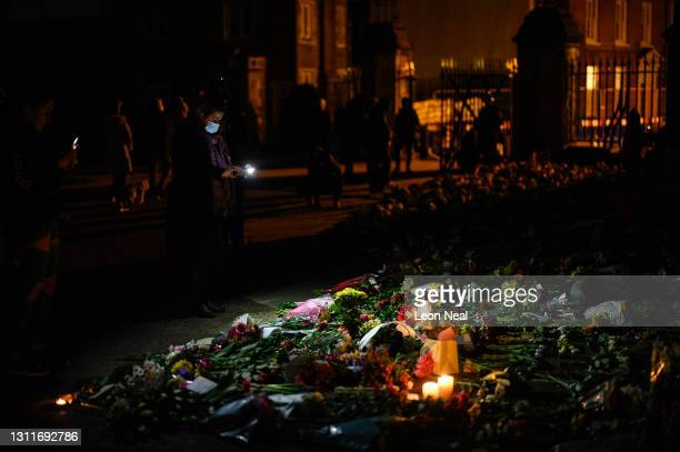 People use their phones and torches to look at the floral tributes outside Windsor Castle following the death of Prince Philip, on April 09, 2021 in...