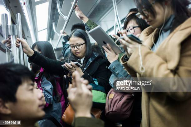 People use their phones in the metro during the morning rush hour in Beijing on November 17 2014 China recorded a betterthanexpected trade surplus of...