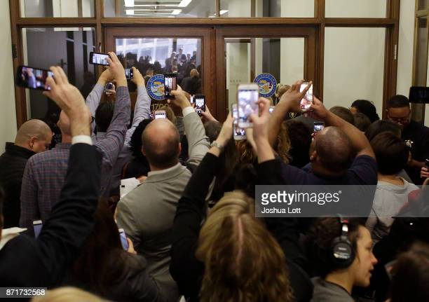 People use their phones to capture former President Barack Obama arriving for Cook County jury duty at the Daley Center on November 8 2017 in Chicago...