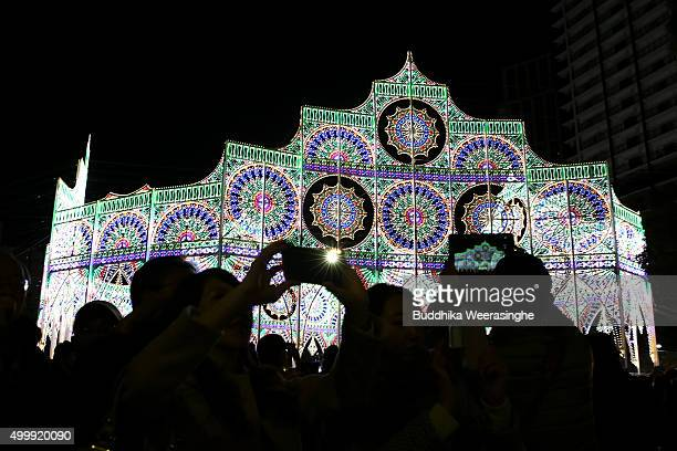 People use their smart phone and take pictures under an illuminated structure as a part of the 21th Kobe Luminarie on December 4 2015 in Kobe Japan...