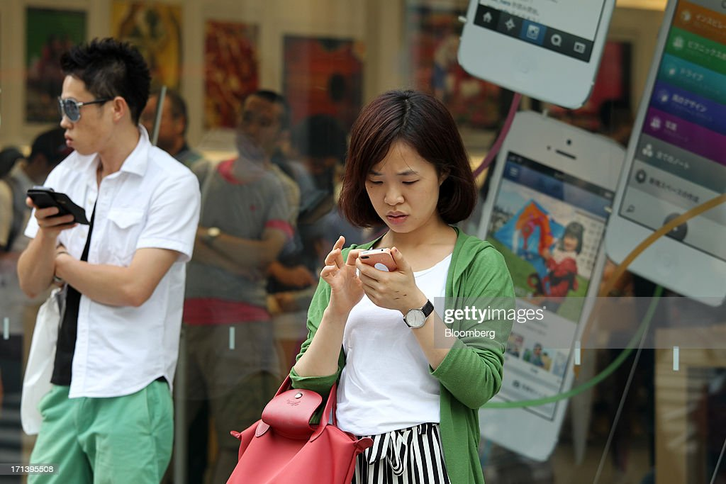 People use their smart phones in front of an Apple Inc. store in the Ginza district of Tokyo, Japan, on Sunday, June 23, 2013. Samsung and Apple, the worlds two biggest smartphone makers, have each scored victories in patent disputes fought over four continents since the maker of the iPhone accused Asias biggest electronics maker of slavishly copying its devices. Photographer: Koichi Kamoshida/Bloomberg via Getty Images