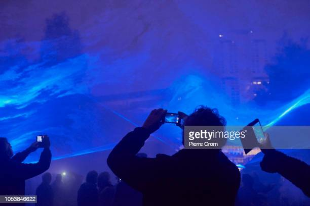 People use their smartphones during the opening of Waterlicht by artist Daan Roosegaarde on October 25 2018 in Rotterdam Netherlands The light and...