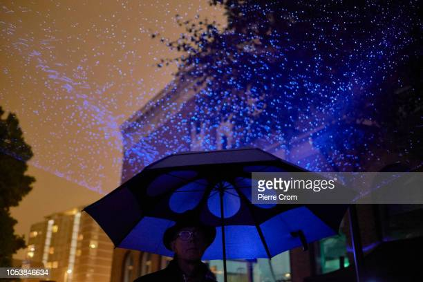 People use their smartphones during the opening of Waterlicht by artist Daan Roosegaarde as rain begin to fall on October 25 2018 in Rotterdam...