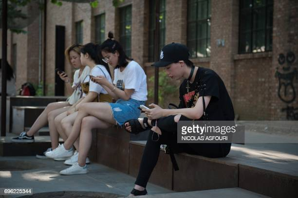 People use their smartphones in the 798 art district in Beijing on June 15 2017 / AFP PHOTO / NICOLAS ASFOURI