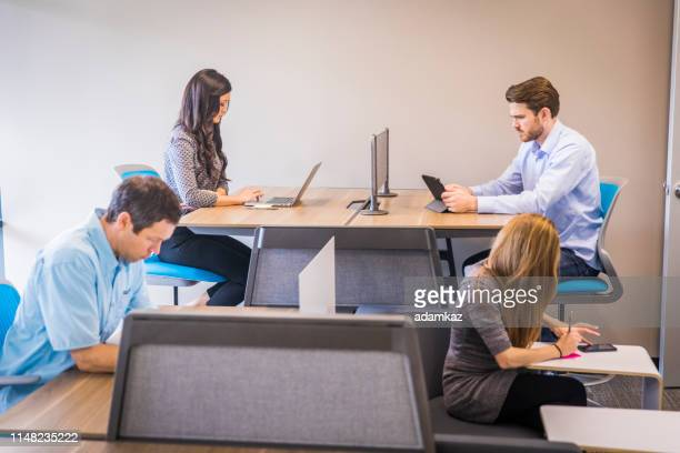 people using a coworking space - mid adult women stock pictures, royalty-free photos & images