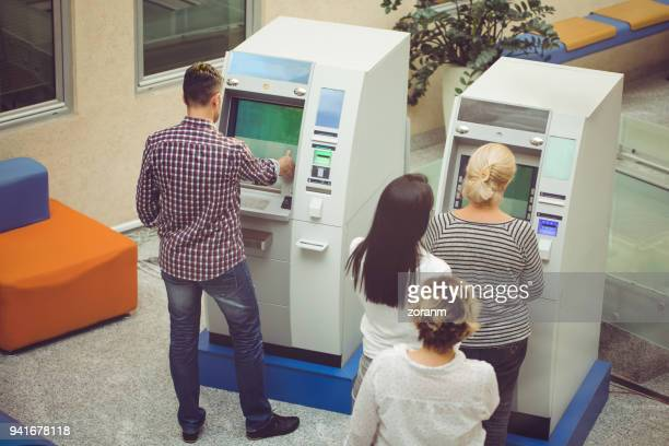 People using ATM machine