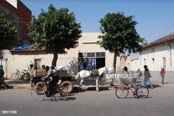 People using bicycles and horses make their way in a street of the Eritrean capital Asmara on November 3 2007 The red and blue logo of USgovernment...