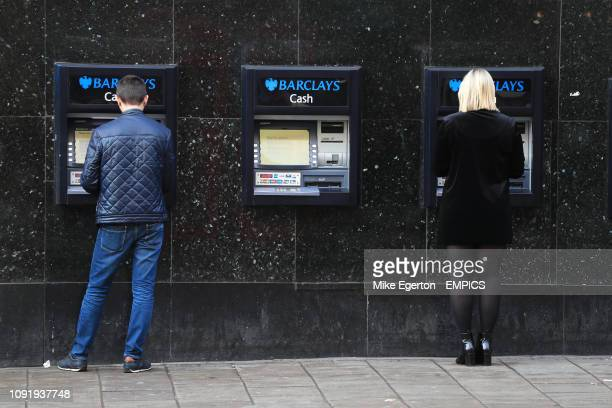 People using cash machines outside a Barclays bank in London. London stock .