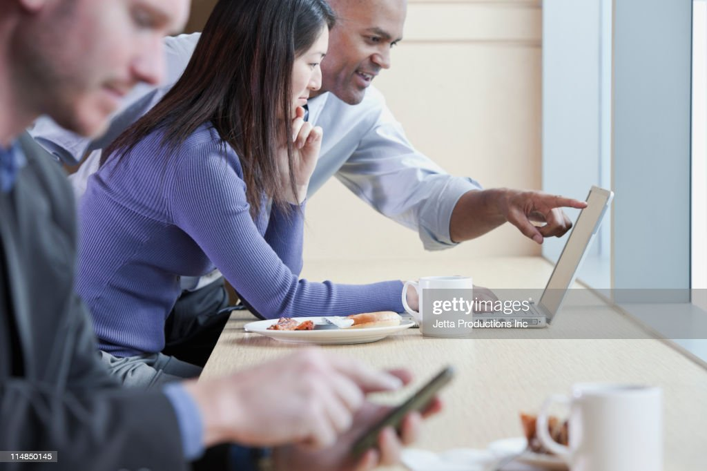 People using electronics in cafe : Photo