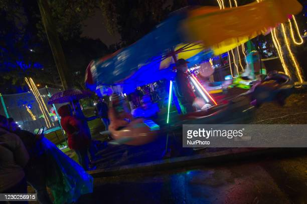 People using protective face masks to prevent the spread of novel Coronavirus pandemic, enjoy the Christmas lights at the National Park in Bogota,...