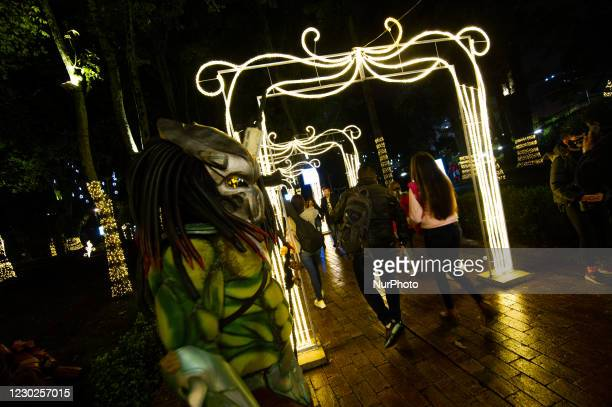 People using protective face masks to prevent the spread of novel Coronavirus pandemic, enjoy the Christmas lights in Bogota's Planetarium in Bogota,...