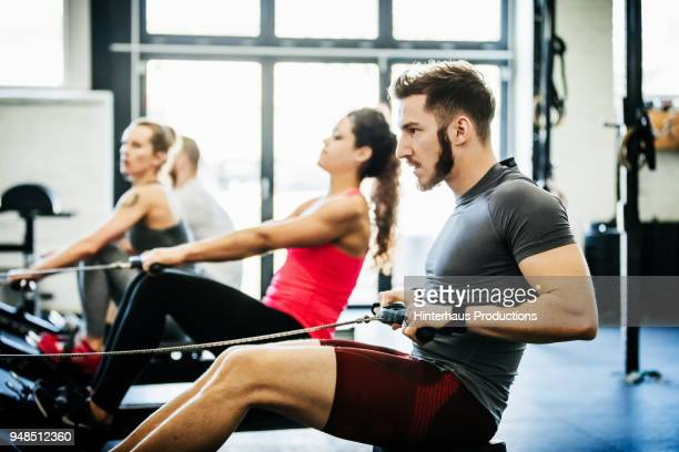 people using rowing machines at gym - black shorts stock pictures, royalty-free photos & images