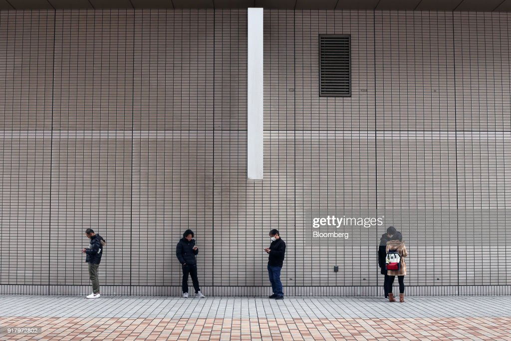 People using smartphones stand outside The Yokohama Sky Building in Yokohama, Japan, on Saturday, Feb. 3, 2018. Japans economy expanded for an eighth quarter, with its gross domestic product (GDP) grew at an annualized rate of 0.5 percent in the three months ended Dec. 31, but the pace of growth fell sharply and missed expectations. Photographer: Takaaki Iwabu/Bloomberg via Getty Images