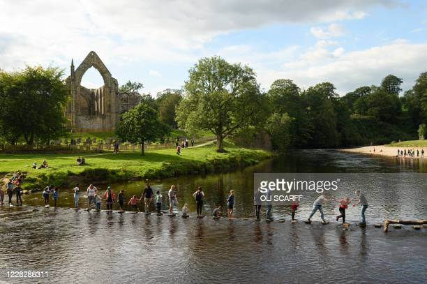 People using stepping stones to cross the River Wharfe at Bolton Abbey near Skipton, on the edge of the Yorkshire Dales National park in northern...