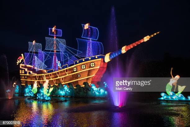 People view a illuminated floating galleon as they enjoy the spectacle at the opening night of annual Festival of Light at the Elizabethan Longleat...