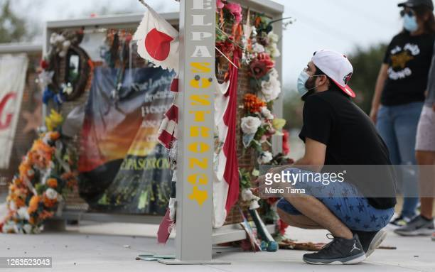 People view a temporary memorial in Ponder Park honoring victims of the Walmart shooting which left 23 people dead in a racist attack targeting...