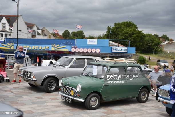 People view an Austin Mini and a Ford Cortina Mk3 during the Southend Classic Car Show along the seafront on June 17 2018 in Southend on Sea England