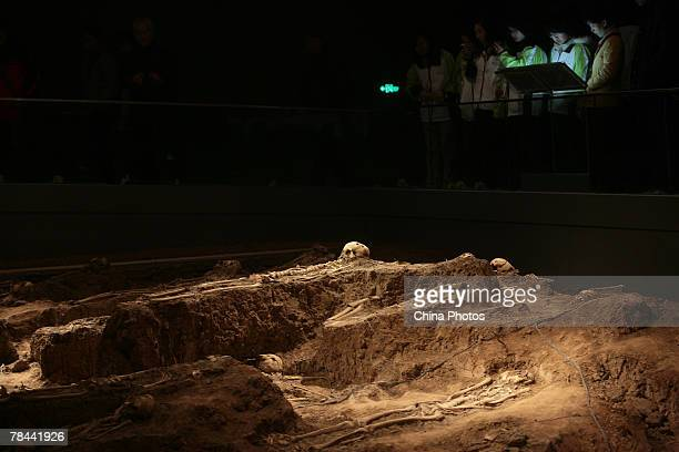 People view an unearthed burial site of victims slughtered during the Nanjing Massacre of 1937 during a ceremony to mark the 70th anniversary at the...