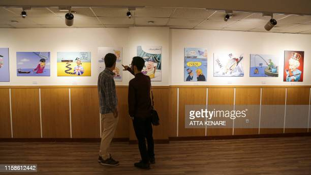 People view caricatures at the Pirates of the Queen cartoon exhibition showing artwork by Iranian artists portraying Britain's Queen Elizabeth II as...