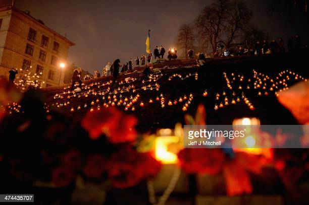People view floral tributes to antigovernment demonstrators killed in clashes with police in Independence Square on February 23 2014 in Kiev...
