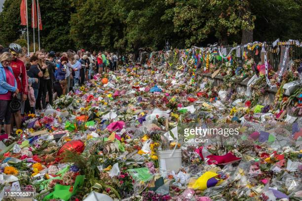 People view flowers and tributes as others nearby take part in a march to remember victims of the Christchurch mosque attacks on March 23 2019 in...