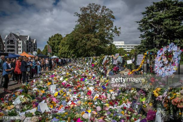 People view flowers and tributes by the botanical gardens on March 19, 2019 in Christchurch, New Zealand. 50 people were killed, and dozens are still...