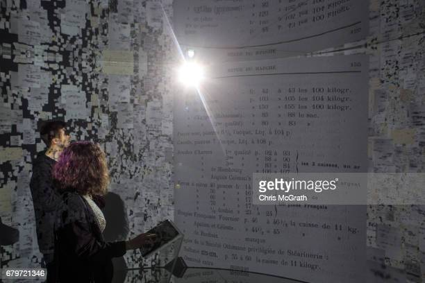 People view historical documents and photographs displayed in a high tech art installation at Salt Galata on May 6 2017 in Istanbul Turkey The...