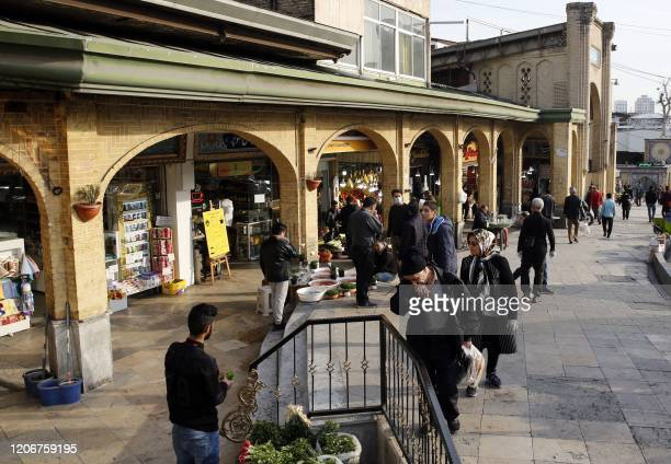 People view items for sale ahead of Nowruz , the Persian New Year, outside the Tajrish Bazaar in Iran's capital Tehran on March 12, 2020. - Iran said...