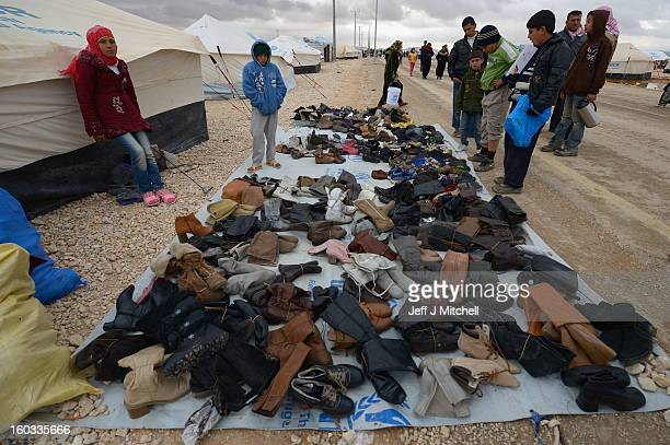 People view shoes for sale as Syrian refugees go about their daily business in the Za'atari refugee camp on January 29 2013 in Mafraq Jordan Record...