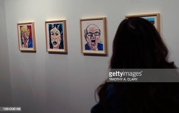 People view the artwork of actor and political cartoonist Jim Carrey during the Outsider Art Fair January 17 2019 at the Metropolitan Pavilion in New...