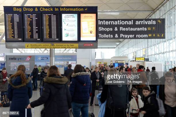 People view the check in information board at London Stansted Airport
