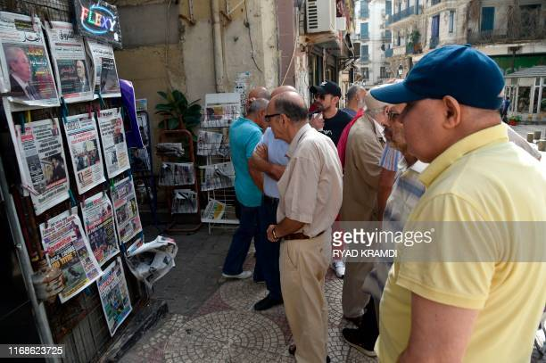 People view the covers of national and foreign newspapers with the announced Algerian presidential election date dominating headlines at a stand in...
