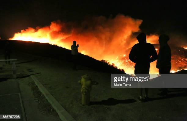 People view the Creek Fire burn on a hillside in the Shadow Hills neighborhood on December 5 2017 in Los Angeles California Strong Santa Ana winds...