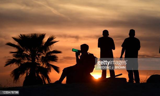 People view the sun set as a child drinks from a water bottle on June 15, 2021 in Los Angeles, California as temperatures soar in an early-season...