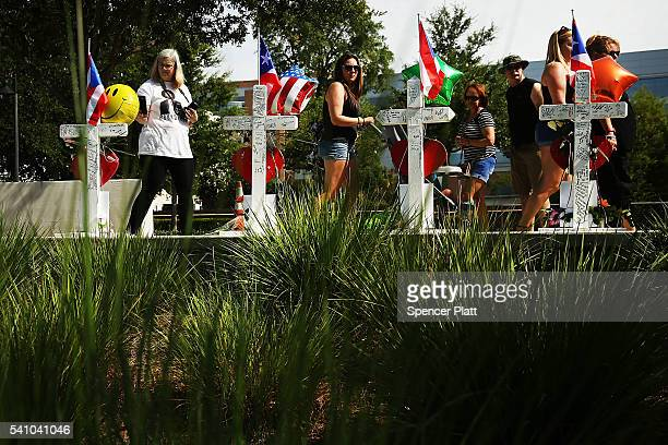 People visit a a memorial down the road from the Pulse nightclub on June 18 2016 in Orlando Florida In what is being called the worst mass shooting...