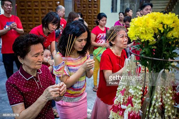 People visit a Buddhist temple during the Chinese New Years Eve say their prayers in front of a Buddha statue with incense and flowers as offerings
