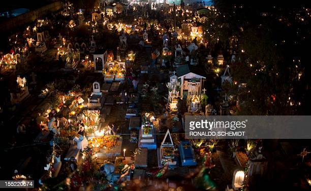 People visit a cemetery in Tlacotepec Puebla State Mexico on November 2 2012 during the commemoration of Mexico's Day of Death The traditional...