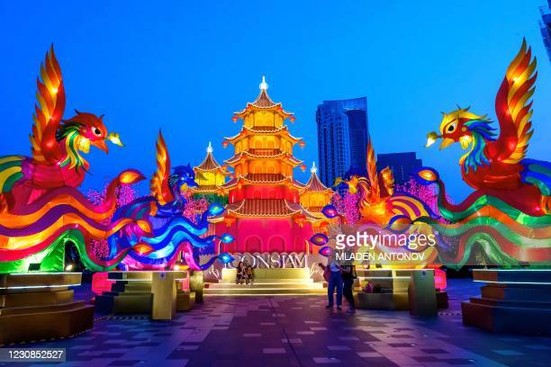 People visit a festive installation of illuminated pagodas and mythical animals erected outside a shopping mall to celebrate the upcoming Lunar New...