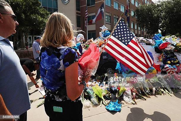 People visit a growing memorial at the Dallas police department's headquarters following the deaths of five police officers on July 10 2016 in Dallas...