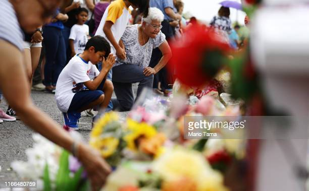 People visit a makeshift memorial honoring victims outside Walmart near the scene of a mass shooting which left at least 22 people dead on August 6...