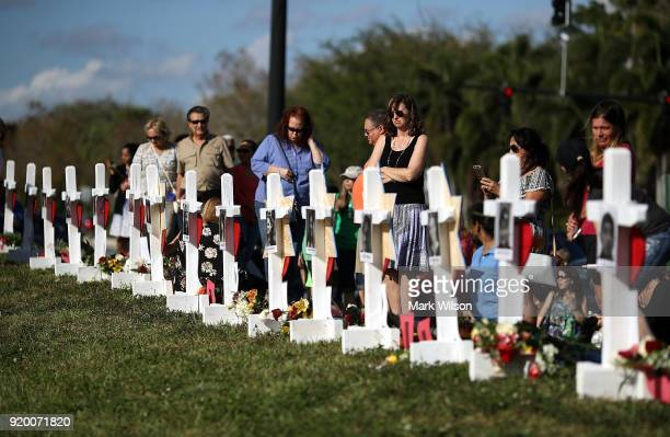 People visit a makeshift memorial in front of the Marjory Stoneman Douglas High School where 17 people were killed on February 14 on February 18 2018...
