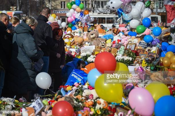 People visit a makeshift memorial in tribute to the victims of a shopping mall fire in the industrial city of Kemerovo in western Siberia on March 29...