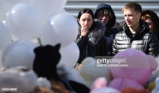 People visit a makeshift memorial in tribute to the victims of a shopping mall fire in the industrial city of Kemerovo in western Siberia on March 31...